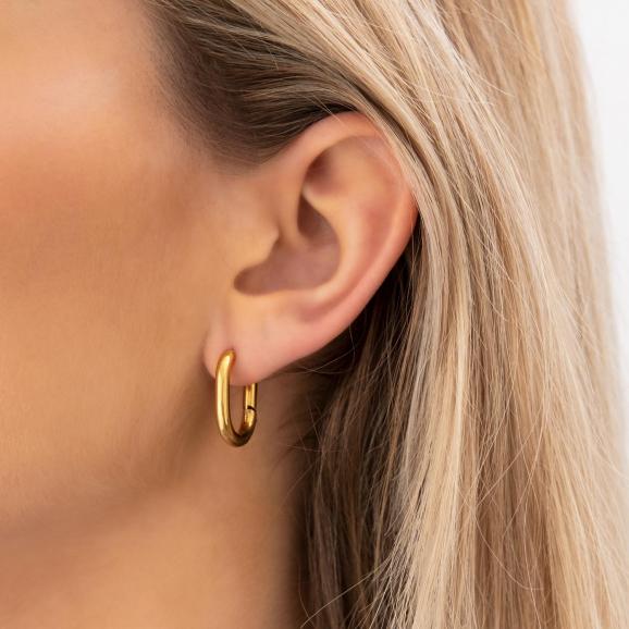 vrouw draagt gouden chunky oorringen met ovale vorm