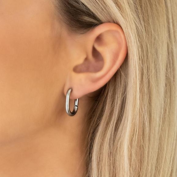 vrouw draagt zilveren chunky oorringen met ovale vorm