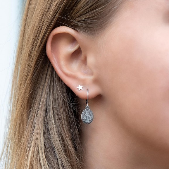 vrouw draagt leuke stud oorbelletjes in het oor
