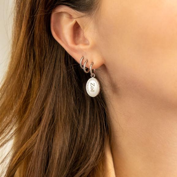 Vrouw draagt graveerbare oorbellen in oor
