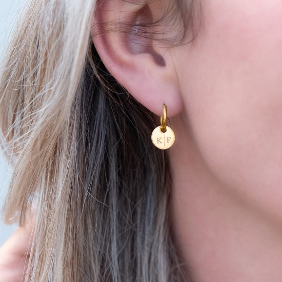 Vrouw draagt gouden oorringetjes met letters in het oor met blond haar