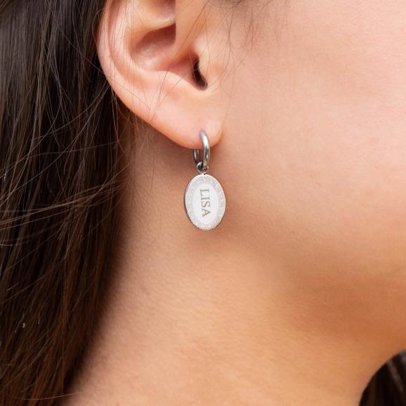 Meisje draagt zilveren ovalen oorbellen met naam