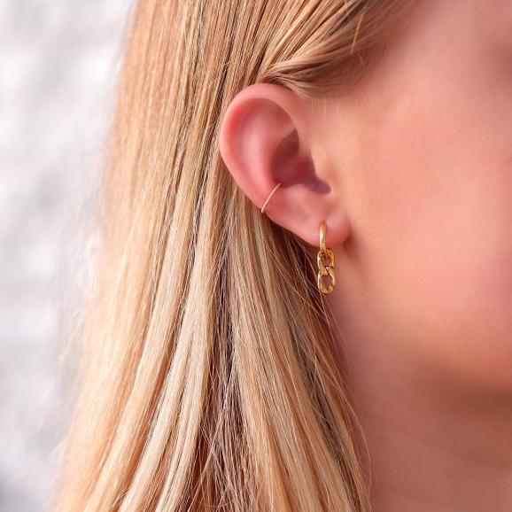 Vrouw draagt leuke schakel oorbellen in voor een complete look