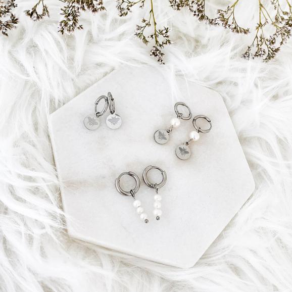 Leuke oorringetjes met parels op een plaatje om te kopen