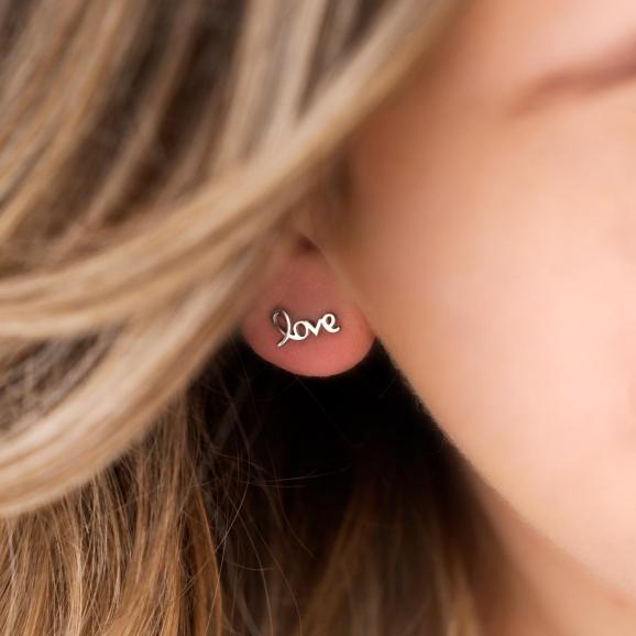 Mooie love oorbellen in het oor voor een complete look
