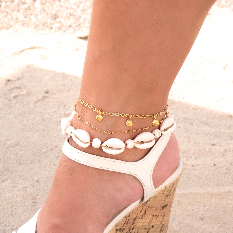 Gouden enkelbandje om de voet met schoen en schelpen