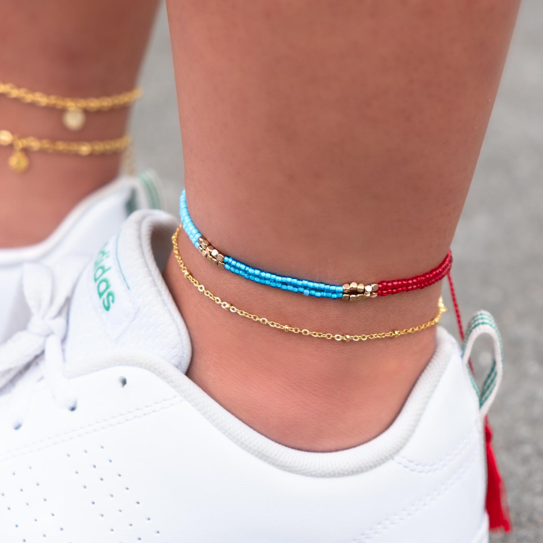 Gekleurde enkelband met kralen om de enkel met schoen