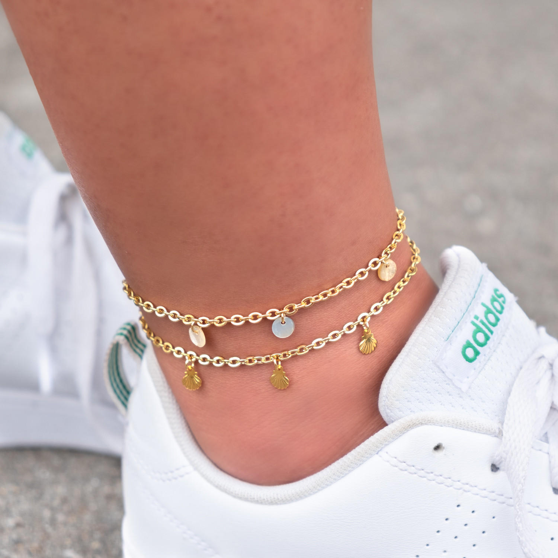 Meisje draagt gouden enkelbandjes om enkel