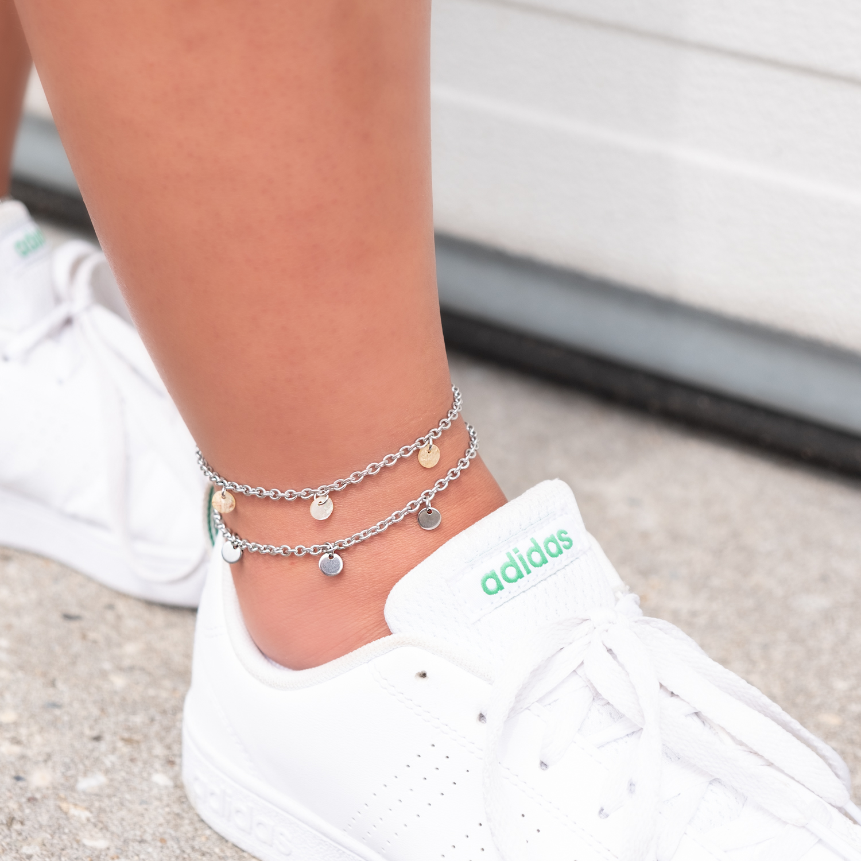 Meisje draagt zilveren enkelbandjes om enkel
