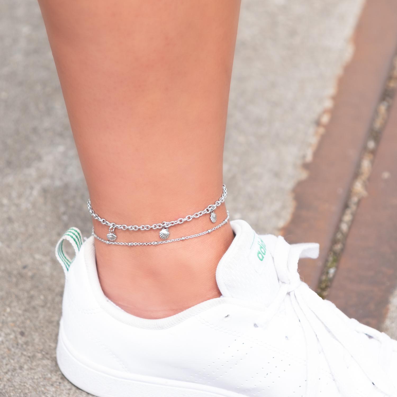 Zilveren enkelbandje met schelpjes en witte sneaker