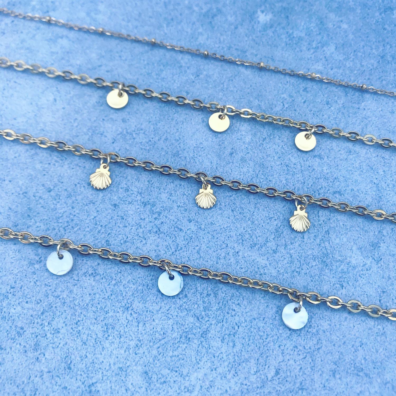 Vier gouden enkelbandjes op grijze ondergrond