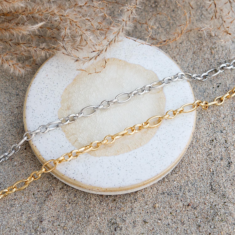 Gouden en zilveren enkelbandjes op plaatje in het zand