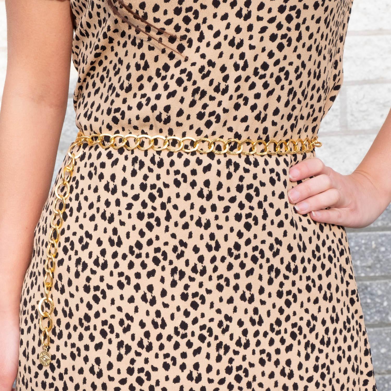 Vrouw draagt gouden chain belt samen met leopard jurkje