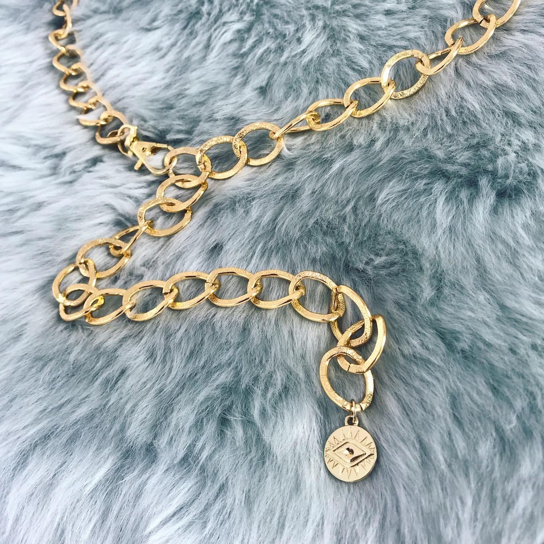 Gouden chain belt op een kleedje met een oogje als hanger