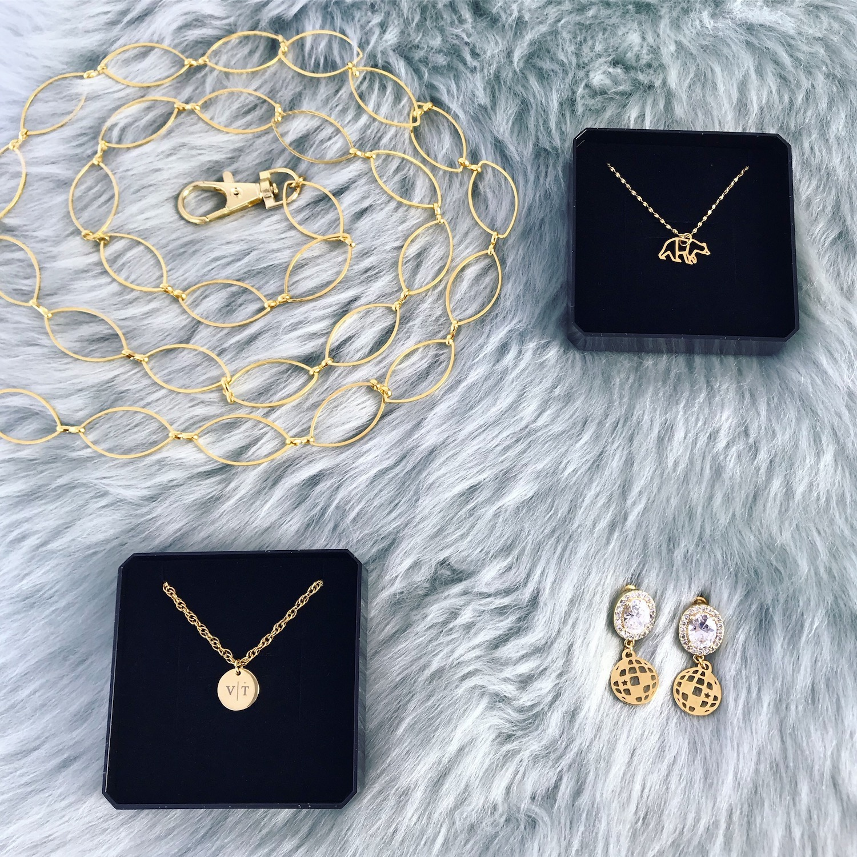 Verschilende gouden sieraden op groen kleedje