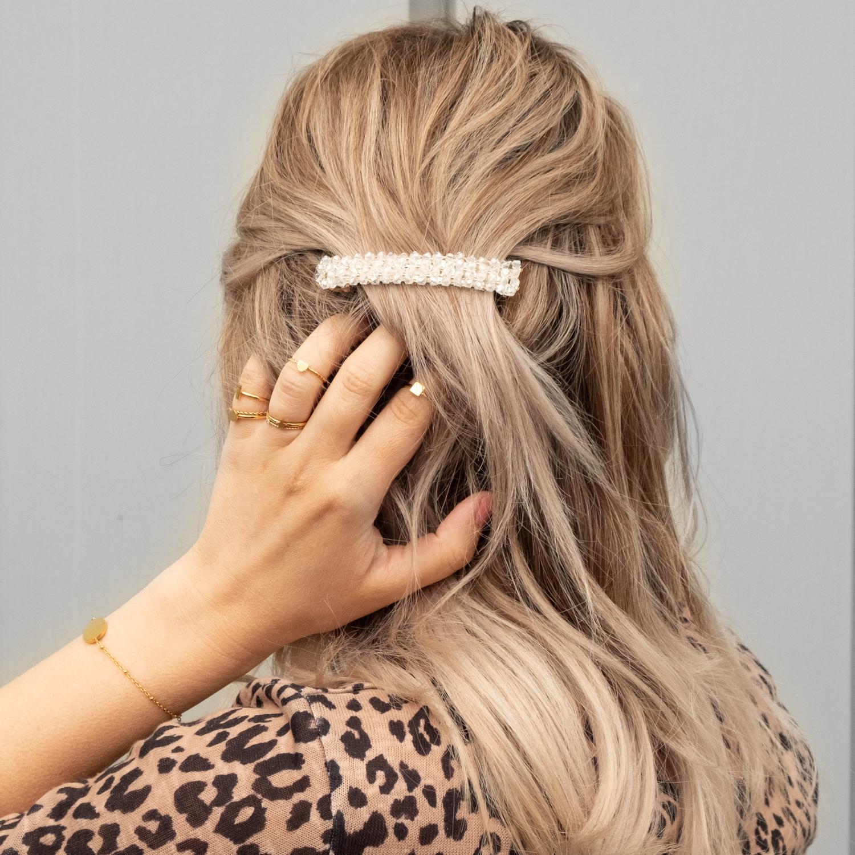 Vrouw draagt verschillende ringen samen met haarspeld