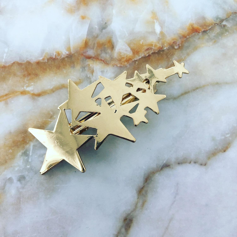Gouden haarclip met sterren op plaatje
