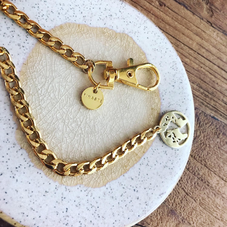 Gouden chain belt met wereldbol op stenen ondergrond