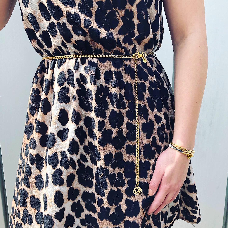 Vrouw met leopard jurkje draagt gouden chain belt