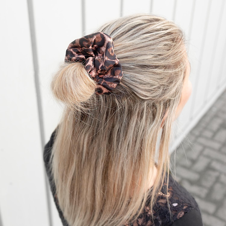 Roze leopard scrunchie in het haar bij een blonde vrouw