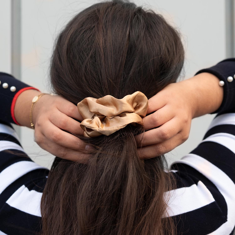Gouden satijnen scrunchie in het haar bij een gestreepte top