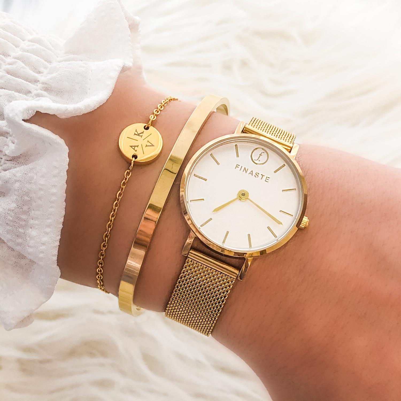 gouden armparty met horloge voor om de pols