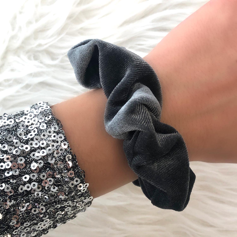 Blauwe scrunchie om de pols voor een complete look