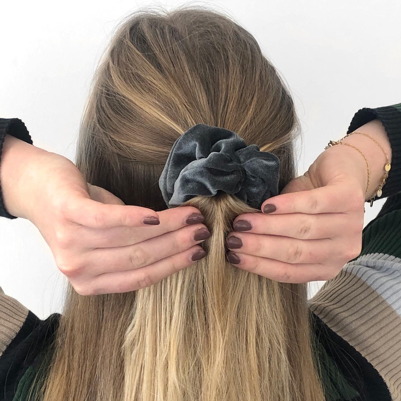 Velourse scrunchie in het haar voor een complete look
