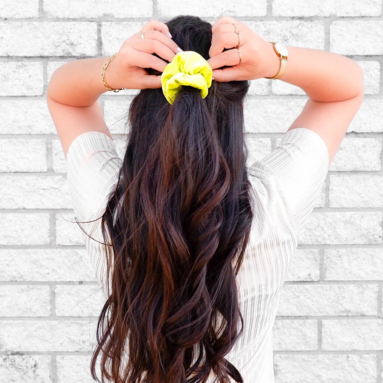 Neon gele scrunchie in het haar voor een trendy look