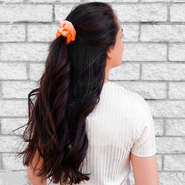 Haaraccessoire in een neon oranje kleur in het haar