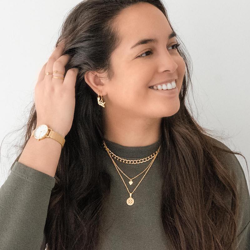 vrouw draagt gouden mix van verschillende sieraden