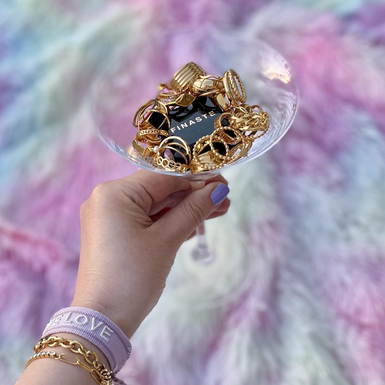 Gouden ringen in cocktailglas en armbanden