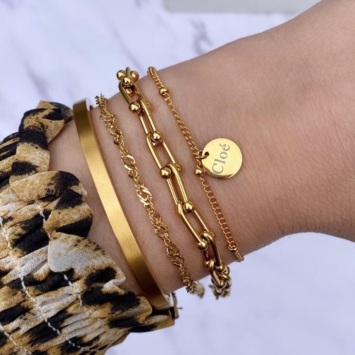 Gouden armparty mix om pols bij vrouw