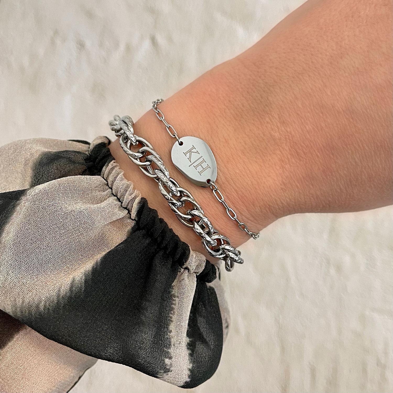 Vrouw draagt graveerbare charm armband om pols