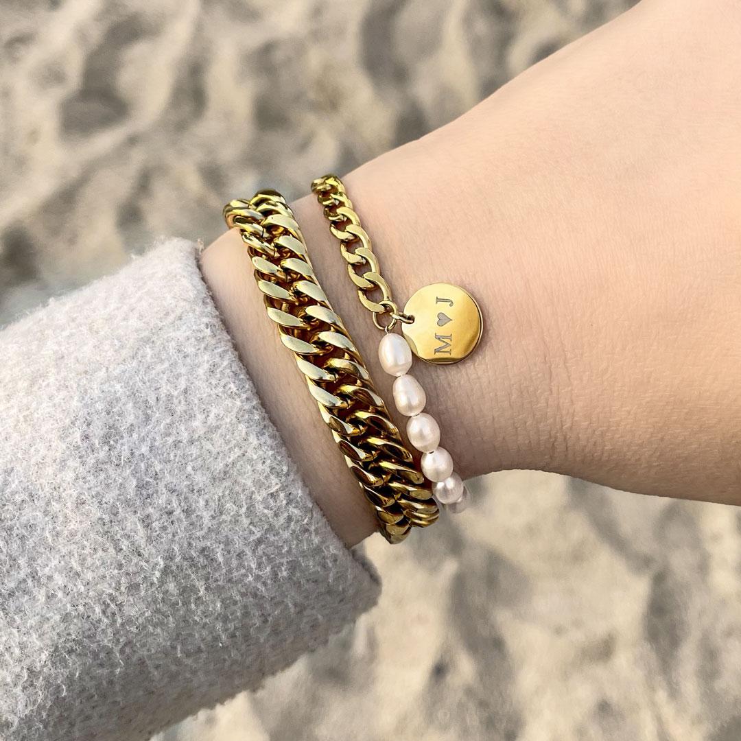 gouden armbanden met parels en gravering om pols
