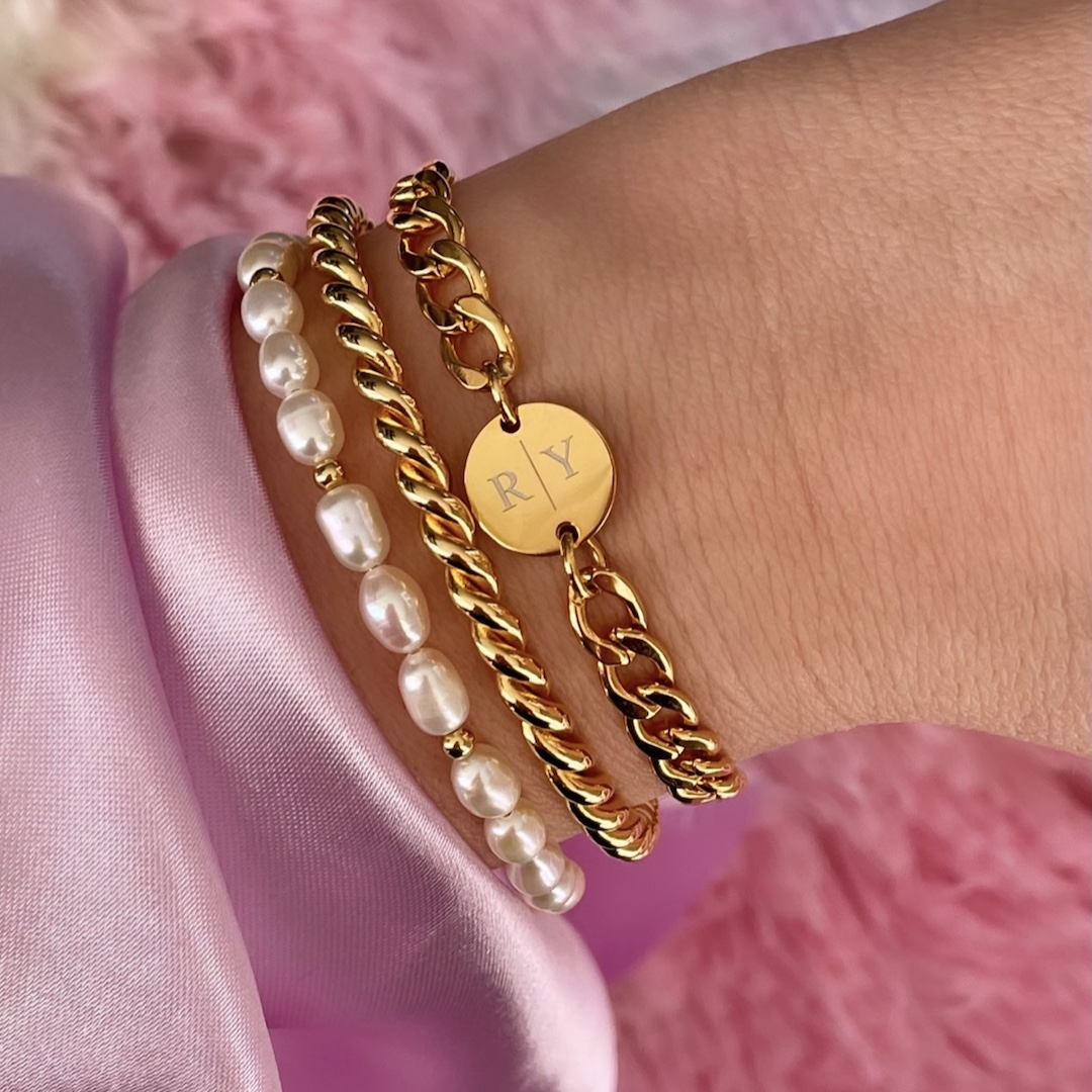 Pols met gouden armbanden met parels en gravering