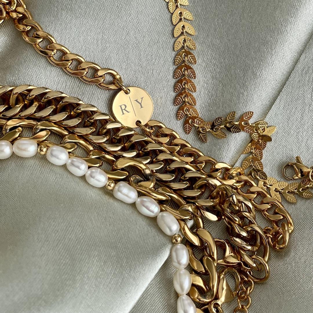 Gouden chain armbanden met parels en gravering op groen satijn