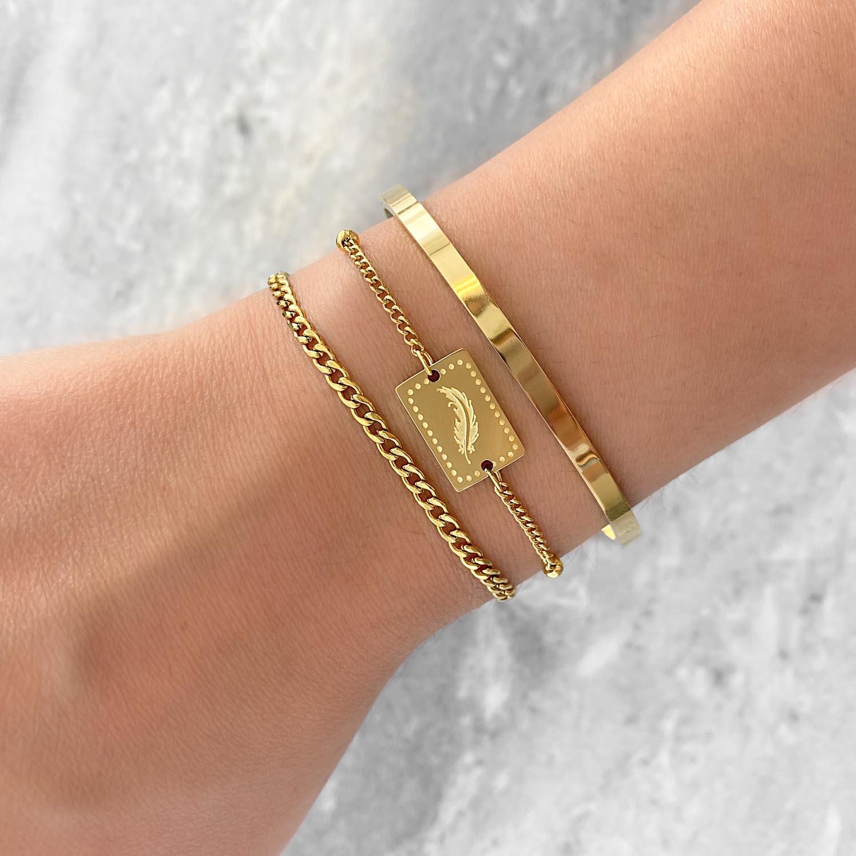 Goudkleurige armband om de pols met een veertje als gravering