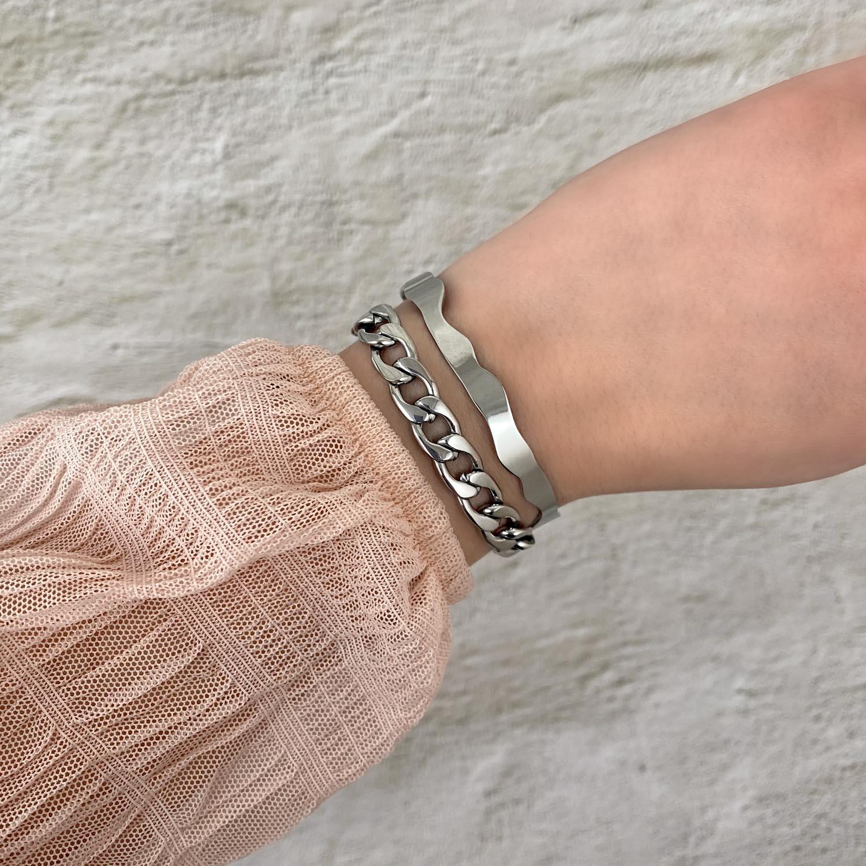 Zilveren armparty met golvende bangle om pols