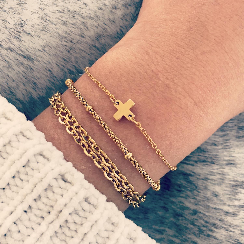 Minimalistische gouden armbandjes gecombineerd met lichte trui