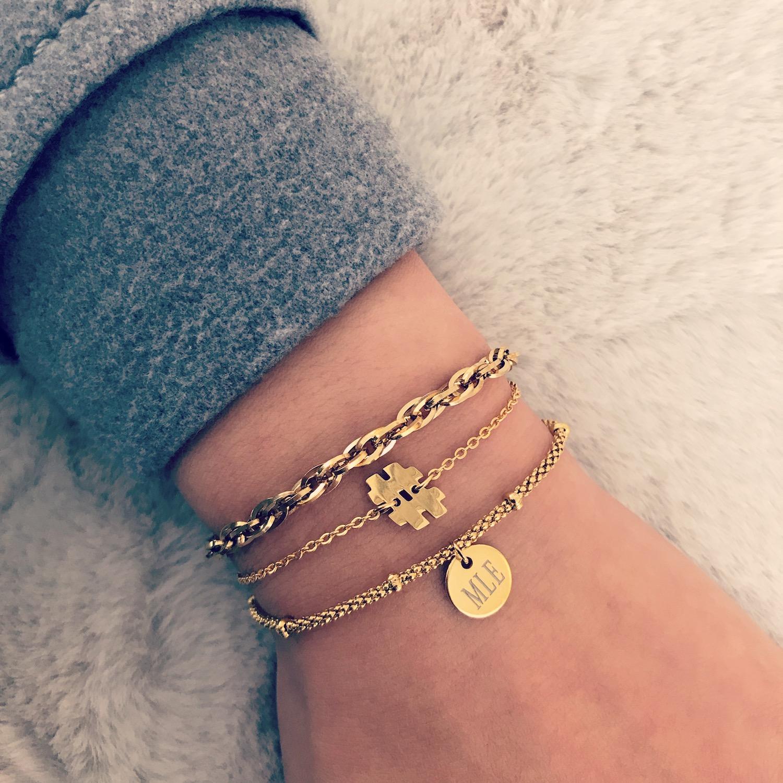 Goud schakelarmbandje gecombineerd met fijne armbandjes