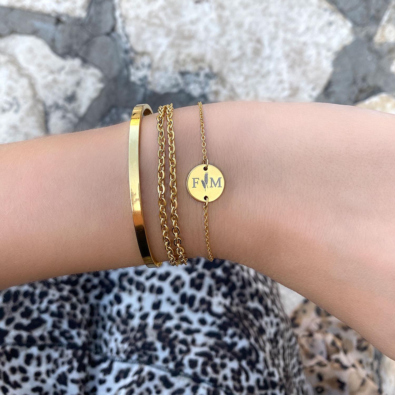 Gouden bangle armband om de pols samen met graveerbare armband