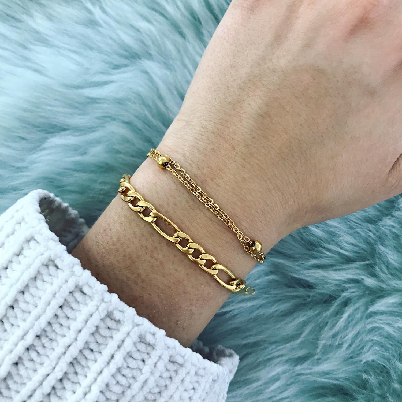 Twee gouden armbandjes gecombineerd bij witte trui