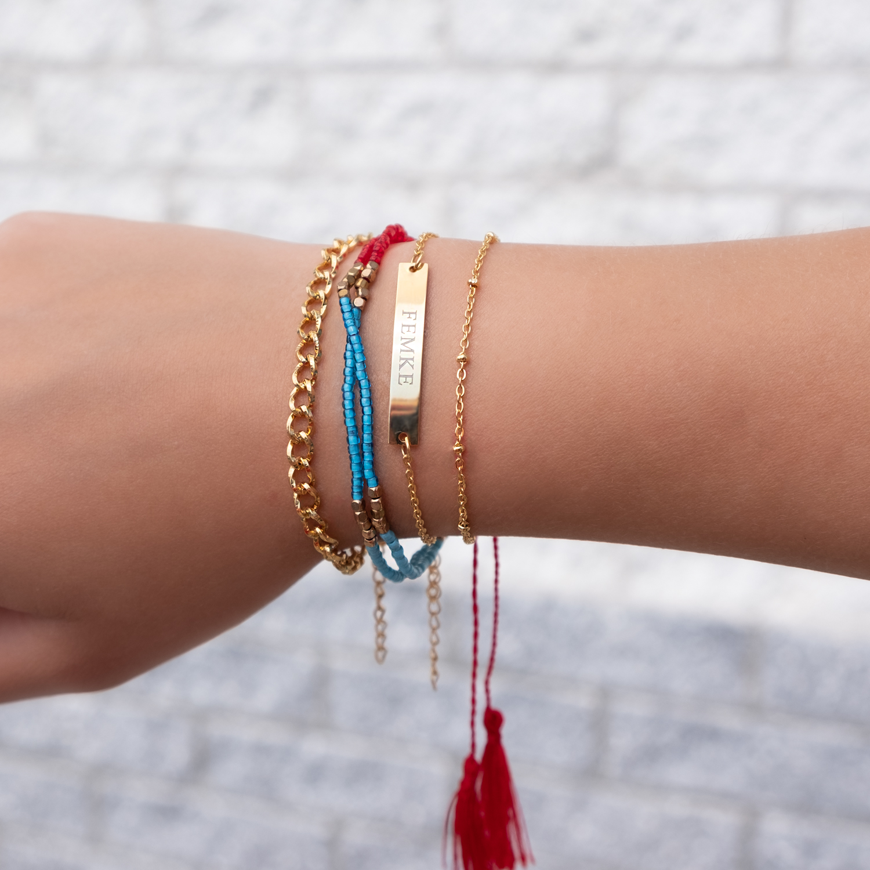 gouden schakelarmband met gekleurde armbandjes en touwtjes