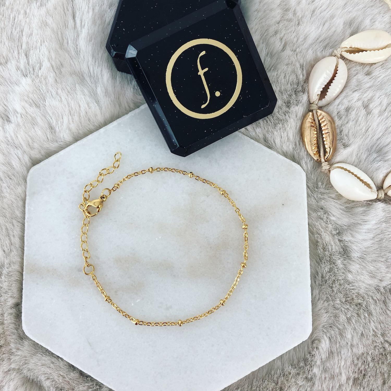 gouden armband met bolletjes op marmer