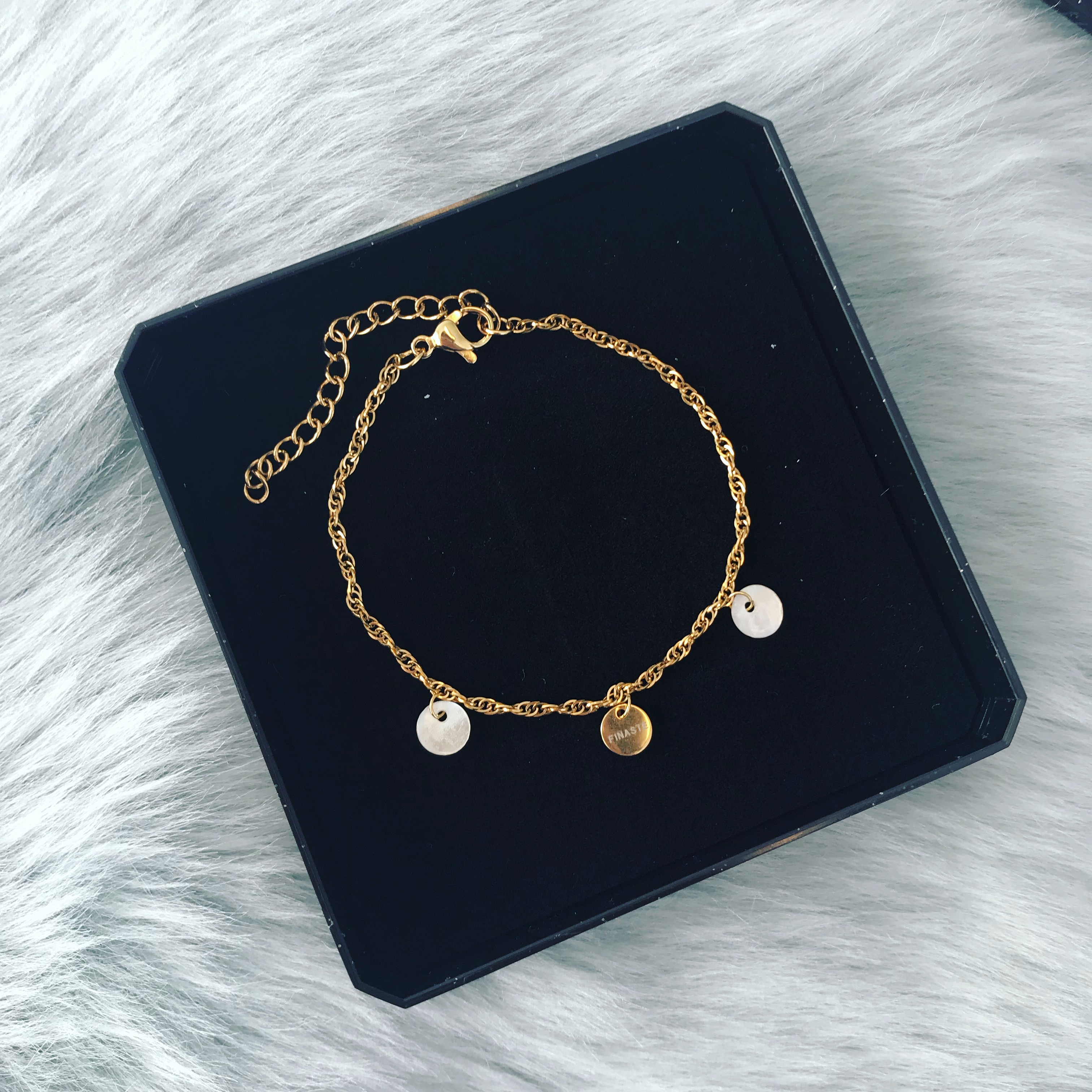 Gouden armbandje met schelpjes en muntje in sieradendoosje