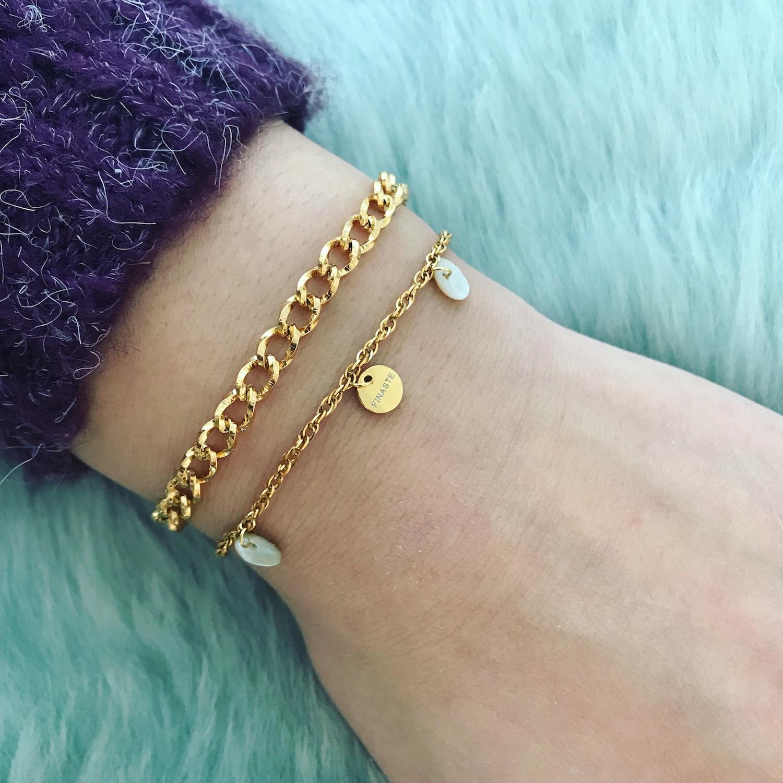 Twee gouden armbandjes met donkere trui en vachtje