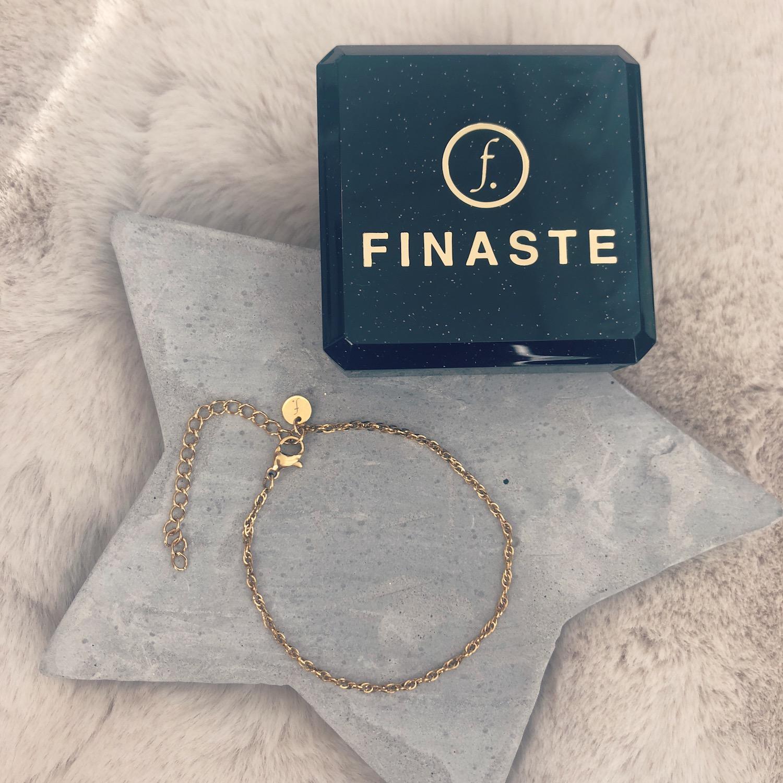 Gouden armbandjes van FINASTE op marmeren achtergrond