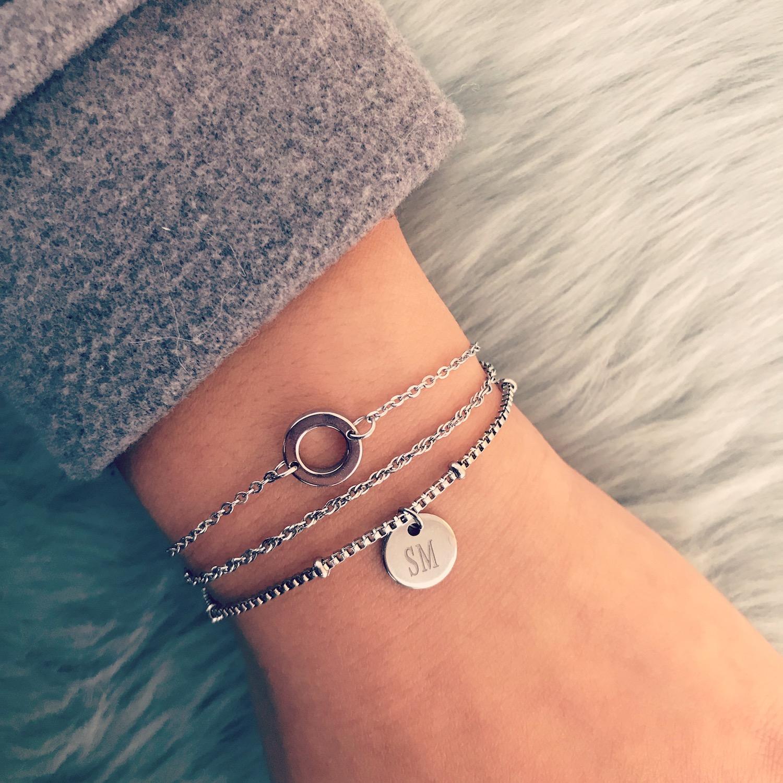 Minimalistische zilveren armbandjes gedragen met grijze trui