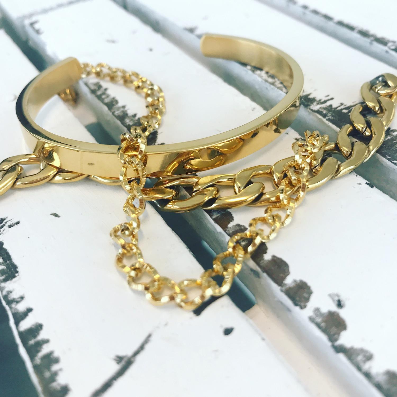 Verschillende gouden armbanden samen op een houten plankje